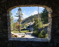 Glacier Point Trail and Amphitheater as seen from Geology Hut. View of glacier point trail and sequioa and pine trees framed by the stone window of a hut, taken royalty free stock photos