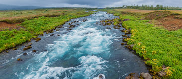 Glacier river. Glacier great fast blue river with green banks in Iceland Royalty Free Stock Images