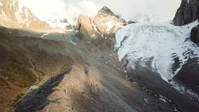 Glacier among rocks. Clouds are visible in the blue sky. Snow-capped mountains and many rocks. Panorama of mountains stock video footage