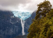 Blue Hanging Glacier with waterfall - southern Chile - Patagonia. Glacier sitting at 1200m high with 19 Km extension. It has a black wall that in the past was royalty free stock photography