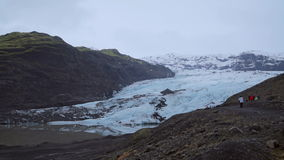 Glacier view. Nordic forecast day. Wide shot of mountain glacier. Forecast and foggy day with some rain. Tourists can be seen around it, size scale can be stock video footage
