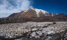 Glaciers glacials sur les pentes du volcan de Tolbachik vues au-dessus d'un champ avec la neige couverte de sable et de cendre photographie stock
