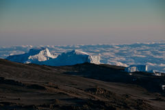 Glaciers of Kilimanjaro. High above the clouds the early morning sun beginning to appear on the glaciers on the crater rim of Kilimanjaro Royalty Free Stock Photo