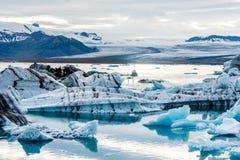 Glacjalna laguna w Iceland, chmurna pogoda, góry na horyzoncie Glacjalny jezioro odbija niebo Zdjęcia Stock