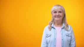 Glad äldre dam som ser till kameran och ler, kund som är lycklig med service arkivfilmer