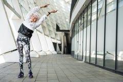 Glad äldre dam som värmer upp vid modern stadsbyggnad royaltyfria foton