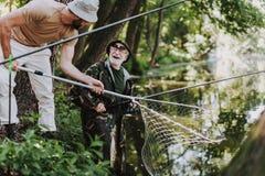 Glad äldre fiskare som tycker om helg med hans son arkivbild