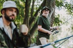 Glad äldre man som tycker om att fiska på helgen royaltyfria foton