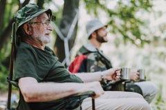 Glad äldre man som tycker om hans fiska helg royaltyfri bild