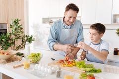 Glad älska fader och hans son som tillsammans lagar mat royaltyfria foton