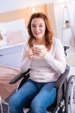 Glad älskvärd rörelsehindrad kvinna som rymmer en kopp Arkivfoto