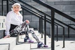 Glad åldrig dam som kopplar av, når att ha klättrat uppför trappan royaltyfri fotografi