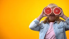 Glad åldrig dam som rymmer två skivor av grapefrukt på orange bakgrund, vitalitet royaltyfri fotografi