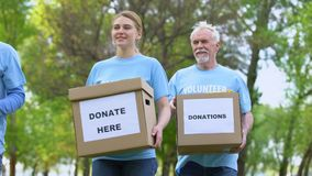 Glad activists with donation boxes walking in park, charity foundation, help stock footage
