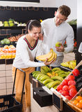Glad adult couple deciding on fruits in shop royalty free stock image