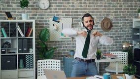 Glad affärsman som lyssnar till musik som dansar att sjunga ha gyckel i regeringsställning lager videofilmer