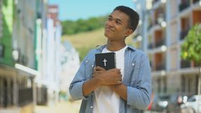 Glad african-american young male hugging holy bible and looking at church, faith