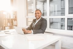 Glad african man working at cabinet and laughing. Waist up portrait of young handsome businessman sitting at office while gaining text on laptop. Guy looking Stock Photography