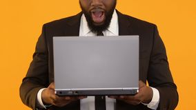 Glad Afro-American man holding laptop and making wow gesture, business e-mail. Stock footage stock footage