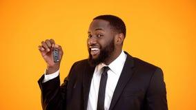 Glad afro--amerikan man i tangenter f?r dr?ktvisningbil och att hyra bilen som leasar arkivfoto