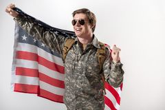 Glad american military young man waving his hand. Joyful male soldier raising his hand while holding a usa flag behind his back. He is smiling and wearing Stock Photo