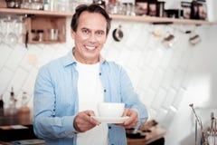 Glad angenäm man som erbjuder dig kaffe royaltyfria foton