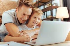 Glad att bry sig man som kramar hans son Arkivbild