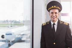 Hilarious smiling pilot in airport. Glad aviator wearing uniform and looking at camera with bright smile. He standing near glass wall. Waist-up portrait. Copy Royalty Free Stock Photo