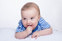 Glad baby. A small boy looking away and sucks his thumb Stock Photo