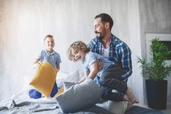Beaming dad having fun with sons. Glad bearded father playing with cheerful kids. He holding small boy in hands. Happy parent and child relationship concept Stock Photos