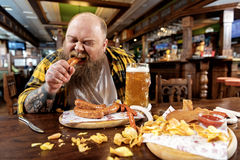Glad bearded man swallowing sausages in tap-room Stock Photography