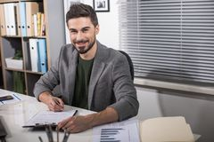 Glad boss underwriting good deal. Waist up portrait of happy businessman sitting at the office desk with pen and papers in hands. Copy space in right side Royalty Free Stock Photos