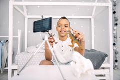 Glad boy blogger learning with dinosaurs toys. Historical period. Pleased afro american boy blogger holding dinosaurs toys while recording video Royalty Free Stock Photos