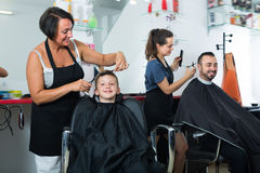 Glad boy sitting in chair and getting hair cut Royalty Free Stock Photography