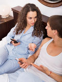 Glad boyfriend and girlfriend busy with smartphones Royalty Free Stock Images
