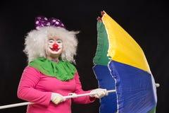 Glad bra rolig clown med ettfärgat paraply på en svart Royaltyfri Foto