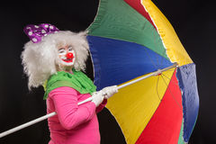 Glad bra rolig clown med ettfärgat paraply på en svart Royaltyfria Bilder