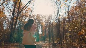 Happy young woman is running in fall day in woodland, frontal view. Glad brunette girl is fleeing in autumn forest in sunny day. She is laughing and smiling stock video