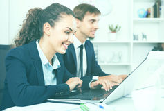 Glad business female assistant wearing formalwear using laptop. Friendly diligent business female assistant wearing formalwear using laptop in company office Stock Photos