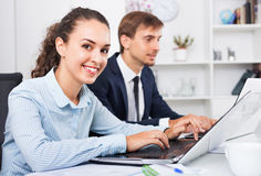 Glad business female assistant wearing formalwear using laptop. Glad friendly efficient business female assistant wearing formalwear using laptop in company Royalty Free Stock Image