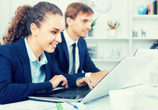 Glad business female assistant wearing formalwear using laptop. Glad smiling  business female assistant wearing formalwear using laptop in company office Stock Photos