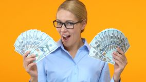 Glad business lady showing bunches of dollars and saying wow, start-up profit stock footage