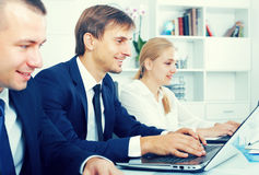 Glad business male sitting with coworkers royalty free stock photos