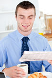 Glad businessman reading newspaper drinking coffee Stock Photo