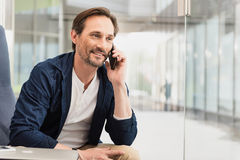 Glad businessman talking on mobile. Portrait of cheerful middle-aged man telling something to his interlocutor by the phone. He is sitting near glass wall and Stock Photo