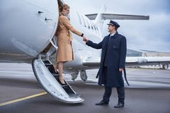 Glad businesswoman descending from airplane with pilot. Side view beaming aviator helping cheerful lady going down from aircraft. Profession and journey concept Stock Photography