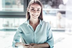 Portrait of pretty female that looking at camera. So glad. Charming girl expressing positivity and holding telephone in both hands while sitting in the office royalty free stock image