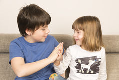 Glad children clasping hands. On a sofa royalty free stock photo