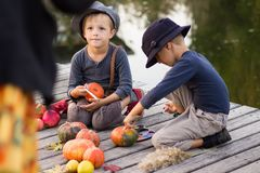 Glad children paint small Halloween pumpkins Stock Photo