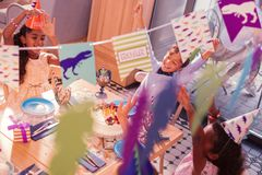 Glad children singing songs and putting hands up at the table. Funny game. Positive relaxed children smiling and putting hands up while singing songs at the stock photo